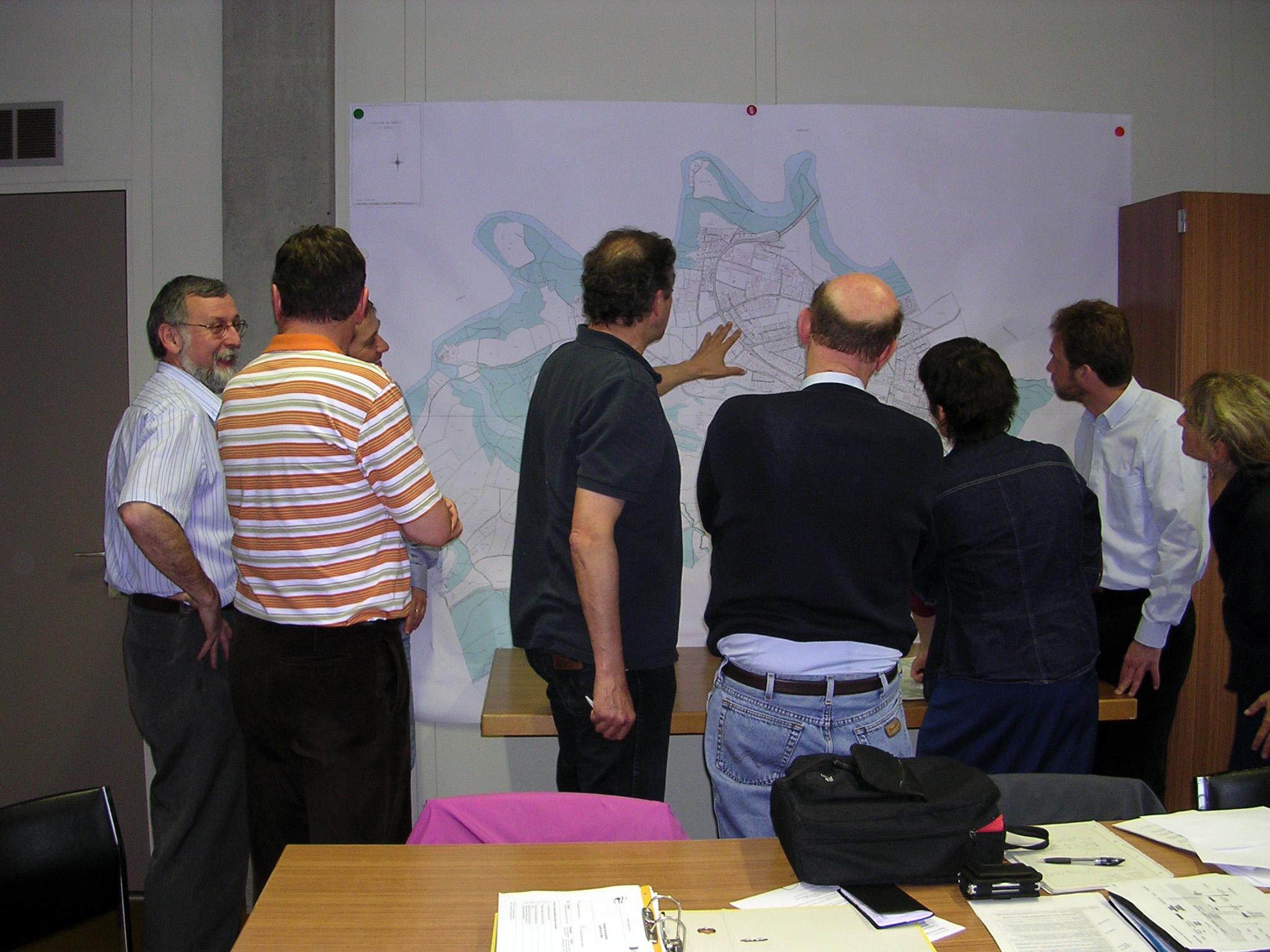 Les membres de la Commission sympa devant la carte de leur commune