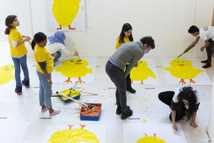 Eine Schulklasse malt Ausstellungsplakate