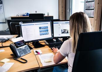 Police cantonale Fribourg - femme de dos travaillant devant un ordinateur