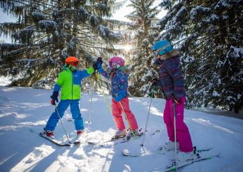 Enfants en tenue de ski sur une piste enneigée