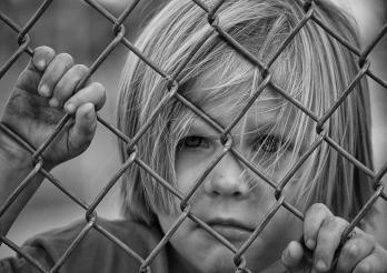 Enfant derrière une grille