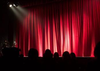 photo d'une scène de théatre avec un rideau rouge