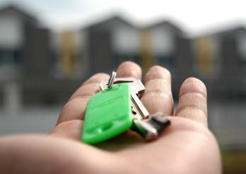 Une main qui tient des clés avec des maisons en fond d'image