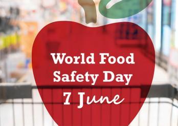 L'image montre le logo choisi par les UN pour la Journée internationale de la sécurité sanitaire des aliments, soit une pomme rouge