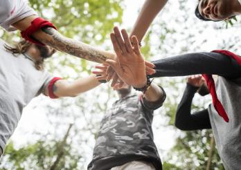 Das Bild zeigt Hände und Armen. Eine davon hat ein tatoo