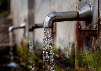 L'image montre un robinet duquel coule de l'eau