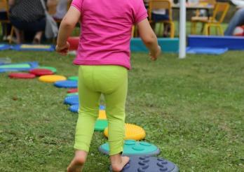 Kleines Mädchen, das von hinten vor einer Gruppe von Kindern und Leuten spielt