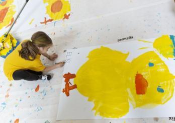 Enfant peignant une affiche poussins