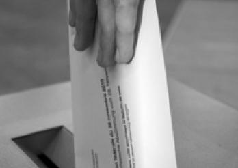 Stimmzettel in die Urne werfen