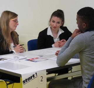 deux représentant-e-s d'une banque  écoutent un jeune élève qui se présente