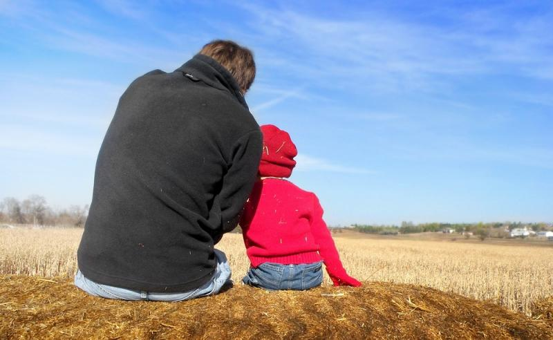 Un père et son enfant assis de dos