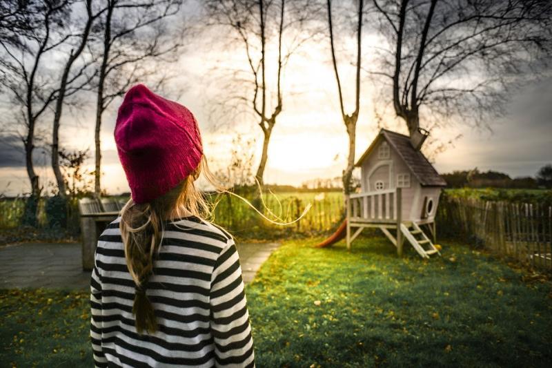 Jeune fille regardant une maison d'enfant