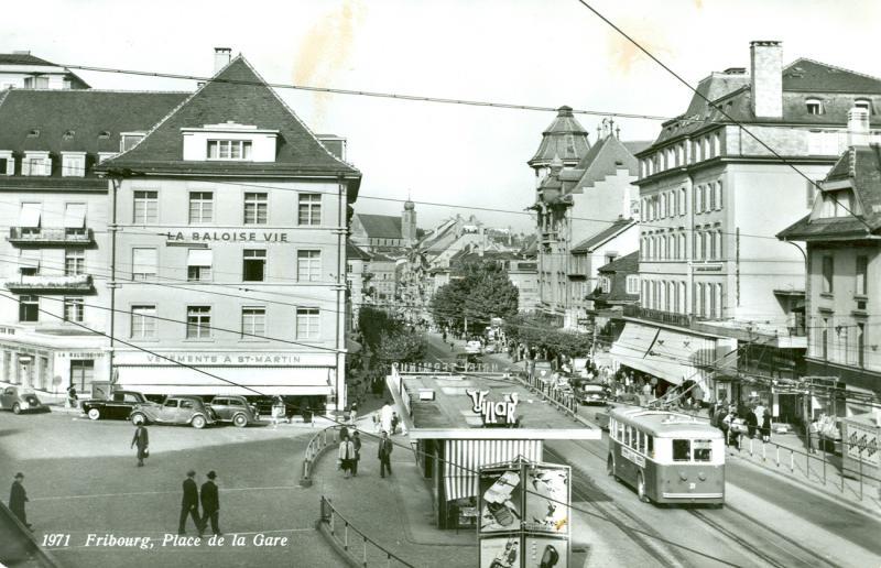 Au croisement des époques, la place de la Gare à Fribourg au temps des trolleybus Saurer (1964-1965), du kiosque de l'hôtel Terminus et de l'Epa-Unip, juste avant la tour de la Bâloise (1964-1965)