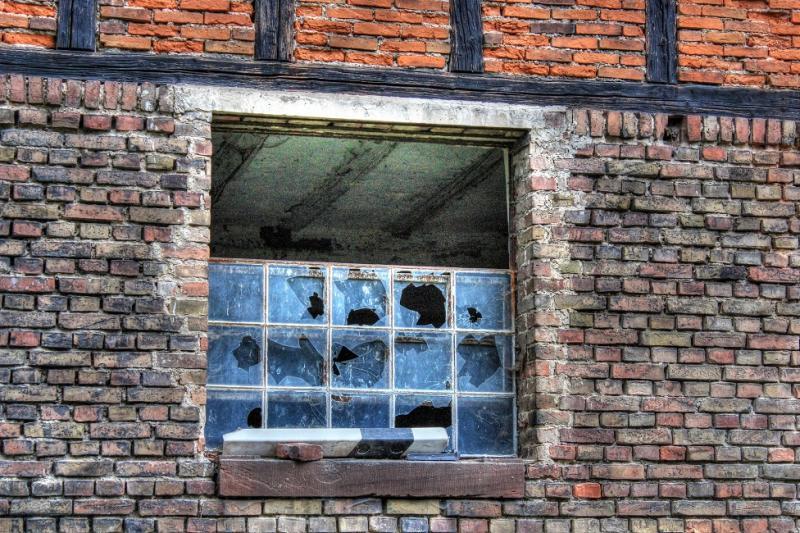 La photo représente une fenêtre cassée d'un étable