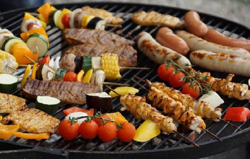 Photo représentant des légumes et de la viande sur un grill