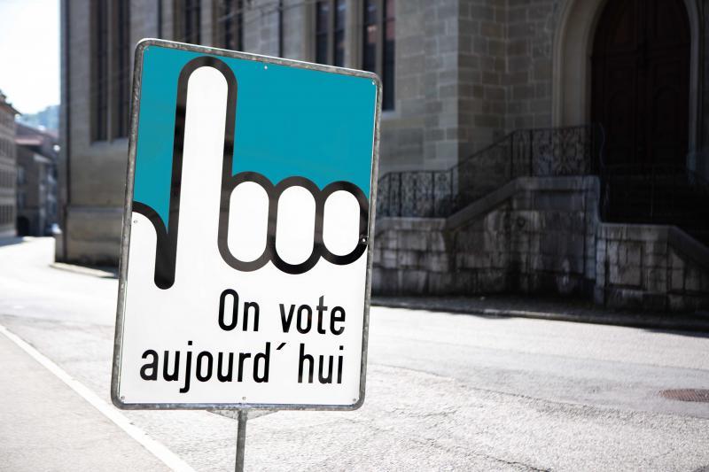 Photographie du panneau avec le doigt en l'air indiquant que l'on vote aujourd'hui