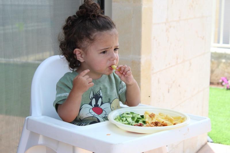 L'image montre une fillette en train de manger