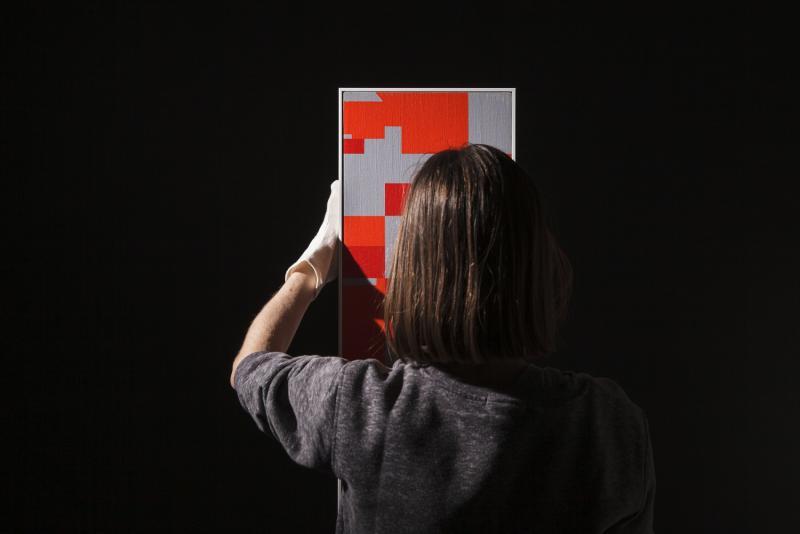 photo représentant une femme de dos qui inspecte un tableau