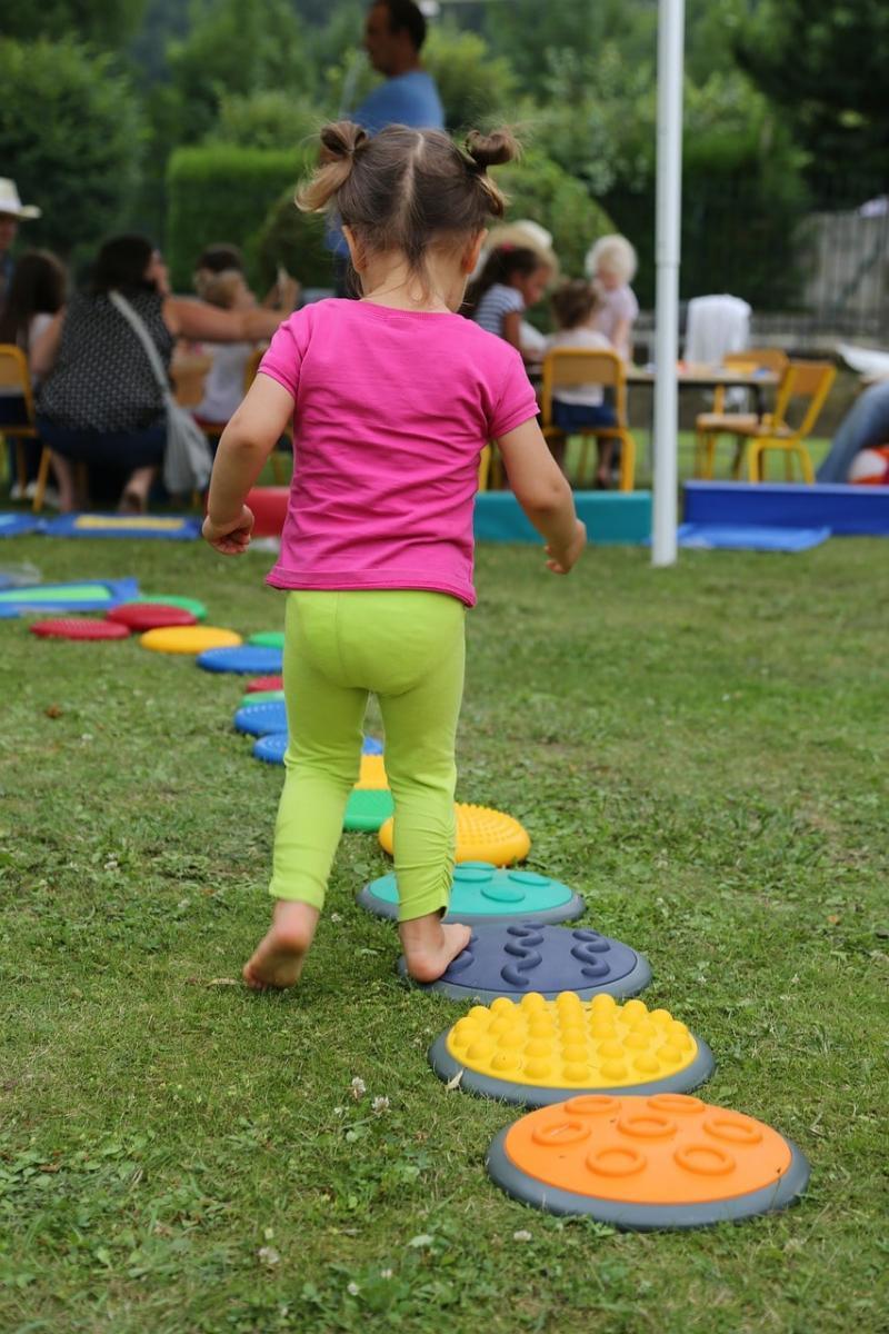 Petite fille qui joue de dos devant un groupe d'enfants et de personnes
